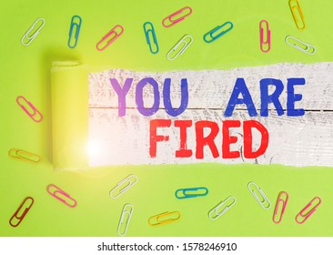Text sign showing You Are Fired. Conceptual photo Getting out from the job and become jobless not end the career Paper clip and torn cardboard placed above a wooden classic table backdrop.