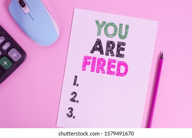 Text sign showing You Are Fired. Conceptual photo Getting out from the job and become jobless not end the career Electronic calculator wire mouse striped sheet pencil colored background.