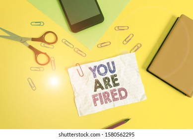 Text sign showing You Are Fired. Conceptual photo Getting out from the job and become jobless not end the career Paper sheets pencil clips smartphone scissors notebook colored background.