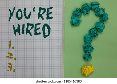 Text sign showing You re are Hired. Conceptual photo New Job Employed Newbie Enlisted Accepted Recruited Notebook paper crumpled papers forming question mark green background.