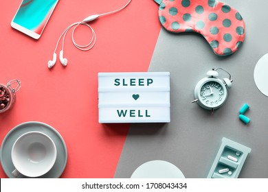 """Text """"Sleep well"""" on trendy lightbox. Coral sleep mask with polka dots, alarm clock, earphones and earplugs. Pills, capsules and calming tea. Flat lay, two tone orange coral and silver background."""