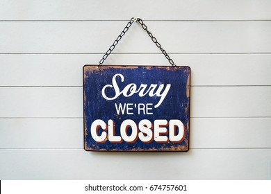 "text ""sorry we're closed"" on rusty metal plate hanging on white wall"