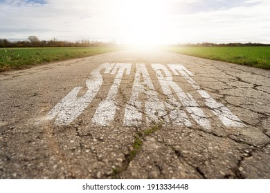text start written on a rural road on the asphalt. concept for beginning. at sunset