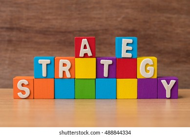 text STRATEGY on stack of colorful wood cube building blocks on wood background