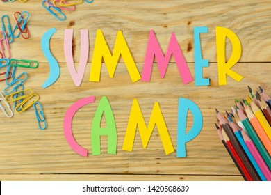 Text SUMMER CAMP of multicolored paper letters and color pencils on a natural wooden background. top view. flat lay