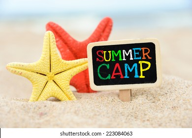 Text Summer camp written with chalk on chalkboard. Text Summer camp written with chalk on chalkboard, on sandy beach side with two sea stars