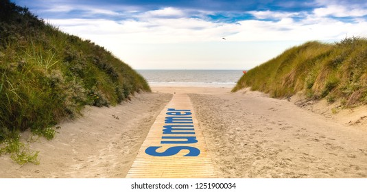 """The text """"Summer"""" written on a wooden path leading to the beach"""