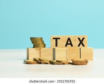 Text TAX on wooden cubes with coins. Business and tax concept.