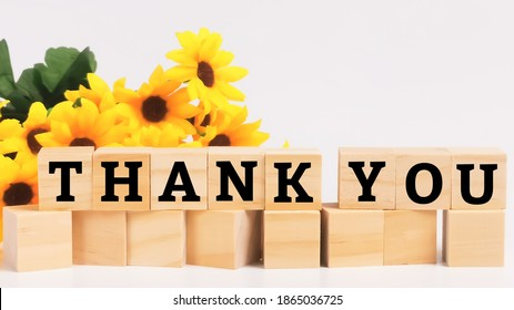 Text thank you on wooden cubes isolated on white background.