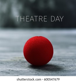 the text theatre day and a cred clown nose on a rustic wooden surface