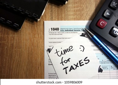 Text time for taxes, US 1040 form, pen and calculator on wooden table