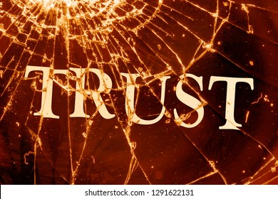 """The text """"Trust"""" on the broken glass. Deceived trust. Lie concept."""
