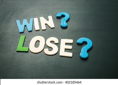 Text 'Win' and 'Lose' wordking on blackboard - colorful alphabet made from wood