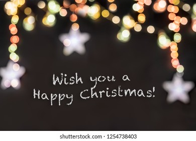 text Wish you a Happy Christmas in black background with blurred colorful stars and light