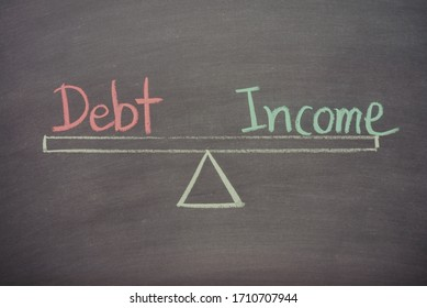 Text word debt and income balance on seesaw drawing writing on chalkboard or blackboard background. Concept of business, personal financial and risk management. Real photo, not illustration.