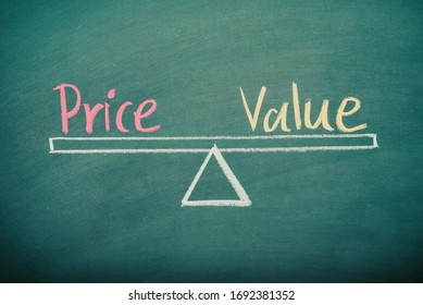 Text word price and value balance on seesaw drawing writing on chalkboard or blackboard background. Concept of price, value analysis in product, business and investment. Real photo, not illustration.