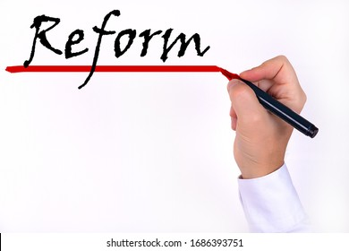 Text, the word Reform, written by a marker which the businessman holds, on a light background. Business concept