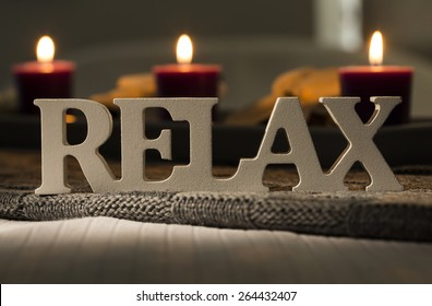 Text of the words relax with burning candles in the background. Relaxation concept for a spa or health retreat