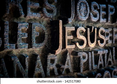 Text written with golden letters. Name Jesus standing out among other names of saints. Beautiful old wall of church in dark colours. Holy and religious place. Famous destination for tourists.
