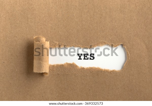The text YES behind torn brown paper