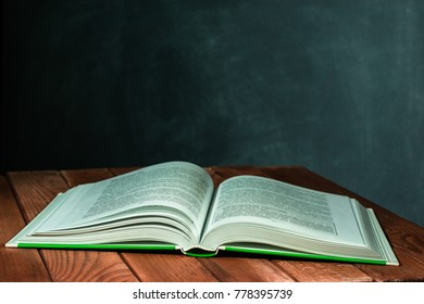 Textbooks and books on a red wooden table. Beautiful dark background.
