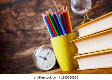Textbooks, clocks, globe and pencils on a wooden background. Educational background