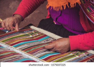 Textile artisan weaving a colorful hand-made blanket in Peru