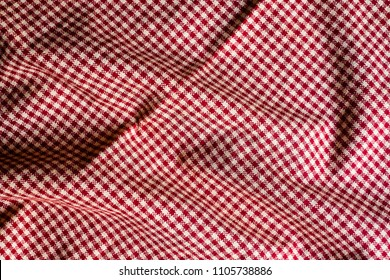 Textile background with a checkered red napkin, top view. Natural textile background. Fabric texture background. Texture of natural linen fabric.