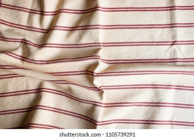 Textile background with a red striped linen napkin, top view. Natural textile background. Fabric texture background. Texture of natural linen fabric.