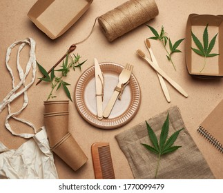 textile bag and disposable tableware from brown craft paper, green hemp leaves on a wooden background. View from above, plastic rejection concept, zero waste