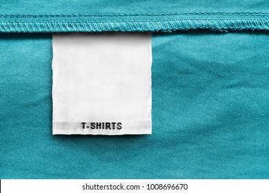 Textile clothes label lettered t-shirts on blue cotton background