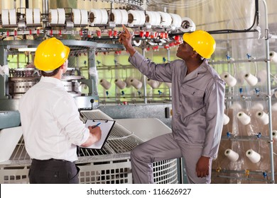 textile factory manager and worker checking yarn on weaving machine