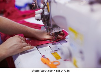 Textile factory workers hands sewing cloth on professional sewing machine