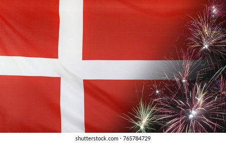 Textile flag of Denmark with firework close up with wind waves in the real fabric