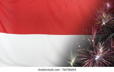 Textile flag of Indonesia with firework close up with wind waves in the real fabric