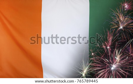 Textile flag of Ivory Coast with firework close up with wind waves in the real fabric
