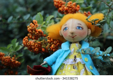 Textile handmade doll with ginger hair and a blue coat in autumn leaves