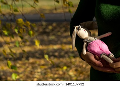 Textile hare toy in multi-colored clothes lying on a woman's hand. Registration of holidays. Interior fairy doll handmade. Art and creativity. Rummy background, there is a place for text.