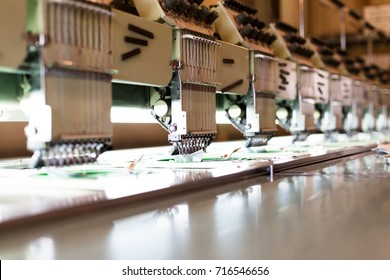 Textile sewing machines in factory hall. Horizontal crop with shallow depth of field