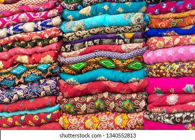 Textiles in vivid colors stacked, ornaments on all of the fabrics.