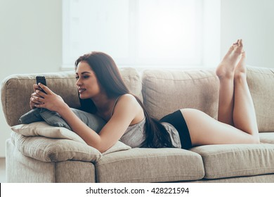Texting to him. Beautiful young woman in panties and tank top holding smart phone and looking at it with smile while lying on couch at home