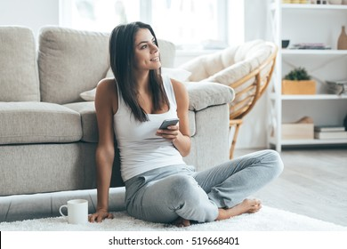 Texting lovely message to him. Attractive young woman holding smart phone and smiling while sitting on the carpet at home