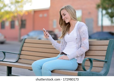 Texting. Woman sitting on a bench outside while using a smartphone.