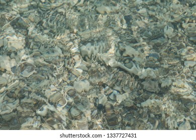 textrured background with pattern of clear sea water above sandy ocean bed.