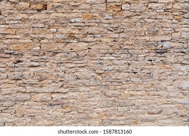 Textural background. Closeup brick stone old aged ancient brown wall