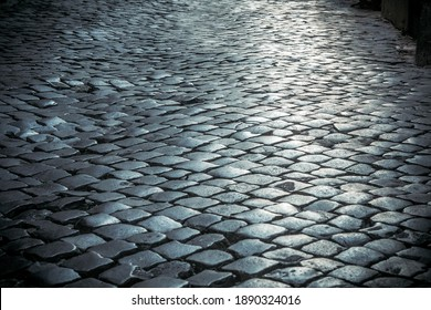 The texture of the ancient road with paving stones. Black paving stones texture. Close-up of an ancient cobbled road.