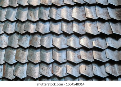 Texture of ancient Roman armor plates, Lorica. Background of rusty chain mail armor from connected plates, close-up. Armor worn from the metallic flakes.