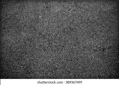 The texture of  asphalt;  Pavement; dark grey asphalt pavement texture with small rocks
