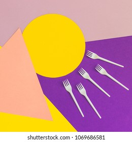 Texture background of fashion pastel colors: yellow, pink and purple geometric pattern papers and plastic forks. Triangles and circles. 90s style