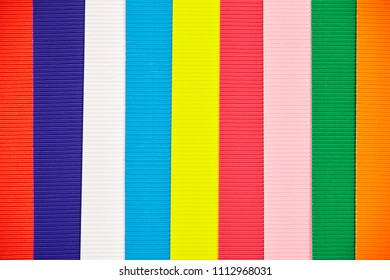 Texture of background with few multi-colored stripes of corrugated paper.